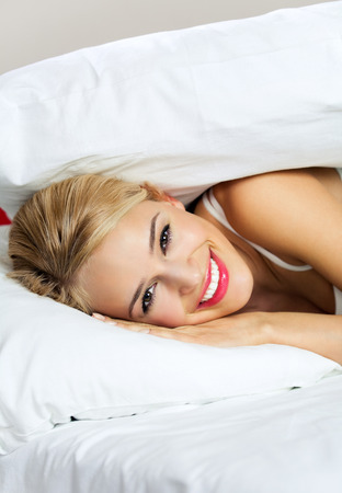 lazyness: Portrait of young happy smiling woman waking up at bedroom