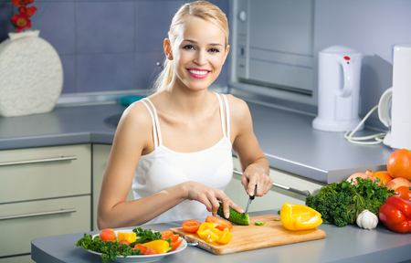 domestic kitchen: Young happy woman making salad at domestic kitchen