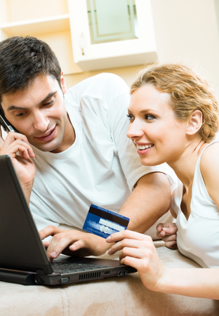house call: Young happy smiling couple with laptop, paying by credit card in internet store, at home