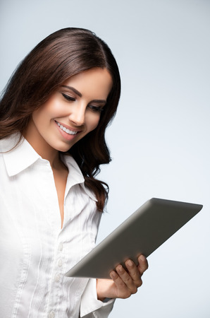 Portrait of happy smiling beautiful young brunette businesswoman using no-name tablet pc, over grey background. Success in business concept studio shot. Stock Photo