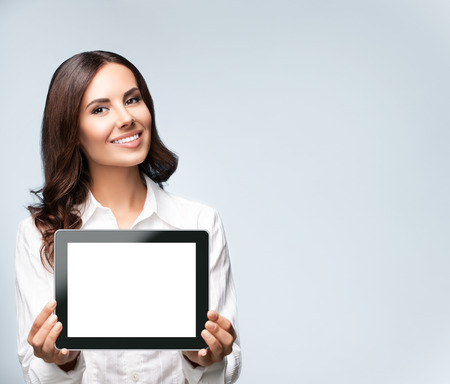 Cheerful beautiful young brunette businesswoman showing blank no-name tablet pc monitor, over grey background, with copyspace area for slogan or text message. Success in business concept studio shot.