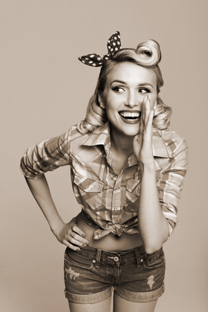 Portrait of beautiful young happy smiling woman, dressed in pin-up style. Caucasian blond model posing in retro fashion and vintage concept. Black and white.