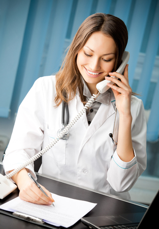 Portrait of happy smiling cheerful young female doctor on phone at office. Medicine and health care concept. Stock Photo