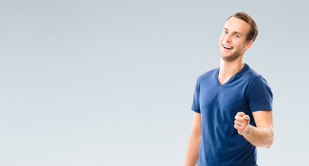about you: What about You? Cheerful young man showing to you with index finger, with blank copyspace area for slogan or advertisiment text, over grey background.  Pointing at something over finger. Emotions and success concept.