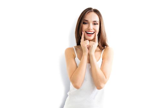 Sorriso da exibição da jovem mulher, na roupa esperta ocasional, isolada contra o fundo branco. Modelo moreno caucasiano nos emoshions e tiro otimista, positivo, feliz do estúdio do conceito do sentimento.