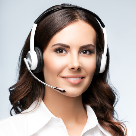 Female customer support phone operator in headset, against grey background. Consulting and assistance service call center. Square composition. Stock Photo