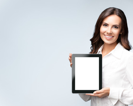 Smiling beautiful young brunette businesswoman showing blank no-name tablet pc monitor, over grey background, with copyspace area for slogan or text message. Success in business concept studio shot. Stock fotó