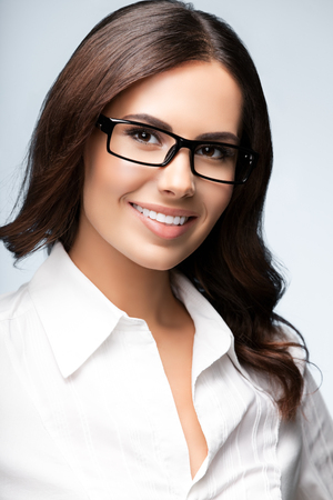 Portrait of happy smiling young brunette businesswoman in glasses, over grey background. Success in business concept studio shot. Stock Photo