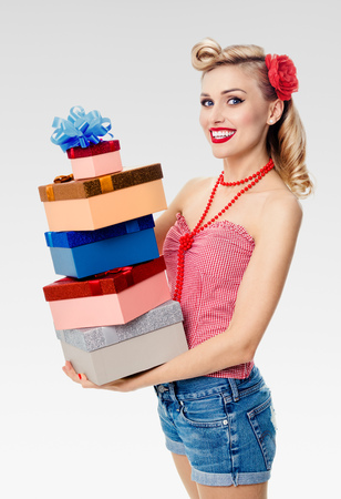 Portrait of beautiful young happy smiling woman in pin-up style clothing, holding gift boxes, on grey background. Caucasian blond model posing in retro fashion and vintage concept shoot. Stock Photo