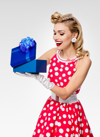 Portrait of beautiful young happy woman dressed in pin-up style red dress in polka dot and white gloves, on grey background. Caucasian blond model posing in retro fashion studio shoot.