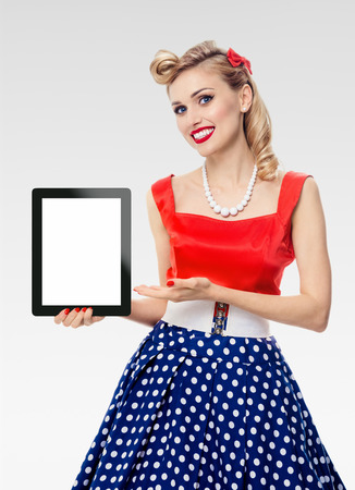 woman, showing blank no-name tablet pc monitor, with copyspace, dressed in pin-up style dress in polka dot, on grey background. Caucasian blond model posing in retro fashion vintage shoot.