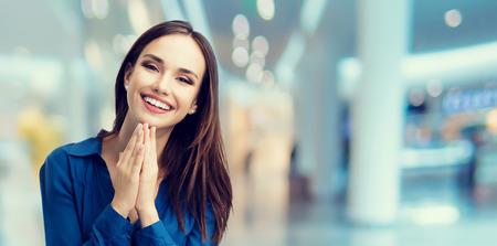 Gesticular feliz mujer joven en el centro comercial o centro comercial sonriendo. Ventas, tienda, venta al por menor, el concepto de consumo. área de copyspace de texto o eslogan publicitario. composición de la bandera. Foto de archivo - 71498361