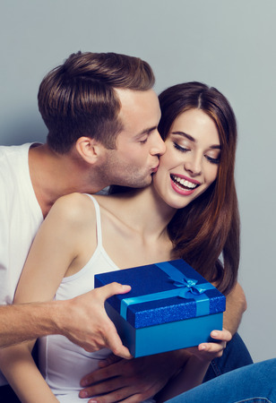 Young happy couple holding blue gift box, sitting close to each other, man kissing woman in cheek. Caucasian models - in love, relationship, dating, lovers, concept shot, against grey background.
