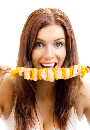 Young happy woman eating shish kebab, isolated on white background photo