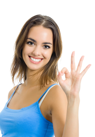 Young happy smiling cheerful woman in sports wear showing okay gesture, isolated on white background