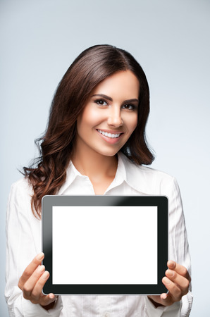Young brunette businesswoman showing blank no-name tablet pc monitor, over grey background, with copyspace area for slogan or text message. Success in business concept studio shot.