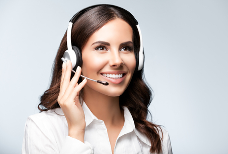 Portrait of cheerful customer support female phone worker, looking up, against grey background. Consulting and assistance service call center. Stock Photo