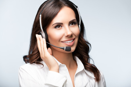 operator: cheerful customer support female phone operator in headset, against grey background. Consulting and assistance service call center.