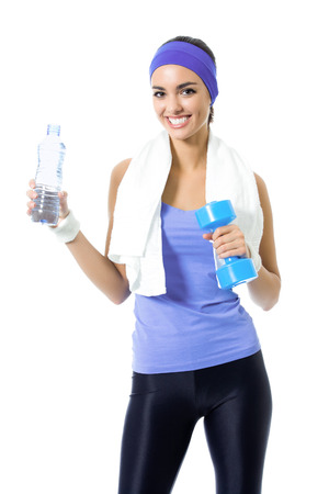 Portrait of happy smiling woman in violet sportswear with bottle of water and dumbbell, isolated over white background. Young female fitness instructor or personal trainer at studio shot.