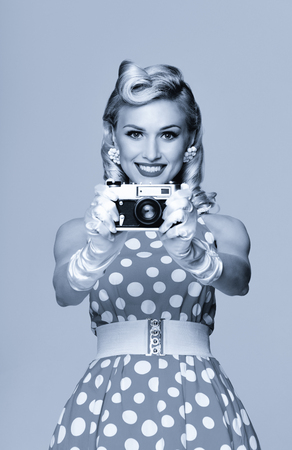 Portrait of beautiful young happy smiling woman, with no-name old film camera, taking picture, dressed in pin-up style. Caucasian blond model posing in retro fashion and vintage concept. Black and white.
