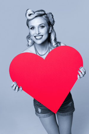 Portrait of beautiful young happy smiling woman holding heart symbol, dressed in pin-up style. Caucasian blond model posing in retro fashion and vintage concept. Black and white. Stock Photo