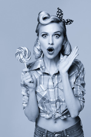 Woman with lollipop, dressed in pin-up style. Caucasian blond model posing in retro fashion and vintage concept. Black and white.