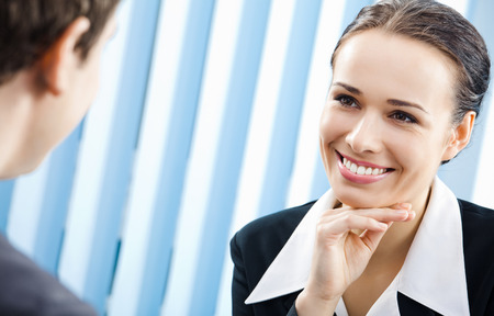 Two happy smiling young businesspeople, or businesswoman and client, working at office. Success in business, partnership and teamwork theme concept. Stock Photo