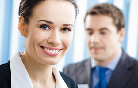 Portrait of successful happy smiling young businesswoman and colleague on background, at office. Success in business, partnership and teamwork theme concept. Stock Photo