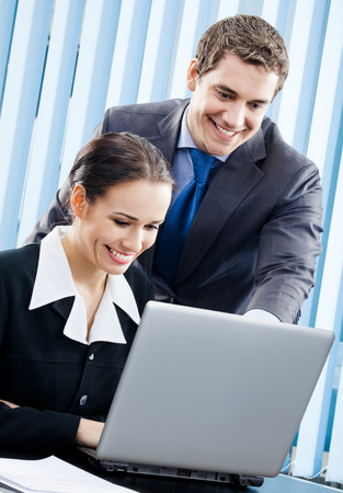 Two happy smiling young businesspeople working with laptop at office. Success in business, partnership and teamwork theme concept. Stock Photo
