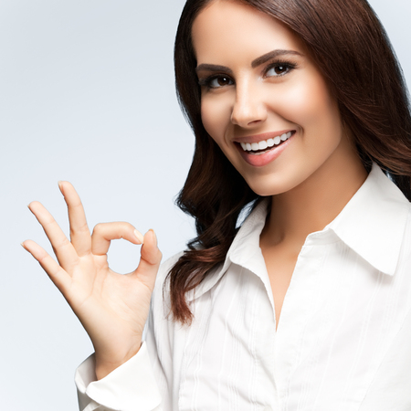 Portrait of happy smiling young cheerful businesswoman, showing okay hand sign gesture, on grey. Success in business concept studio shot.