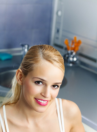 domestic kitchen: Portrait of young happy smiling attractive woman, at domestic kitchen Stock Photo