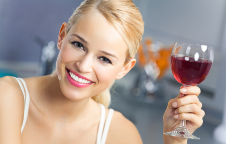 1 woman only: Portrait of young woman with glass of red wine, at home