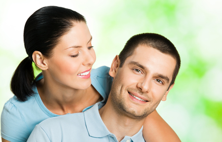 Portrait of young happy smiling attractive couple, outdoors. Love, relations, romantic concept. photo