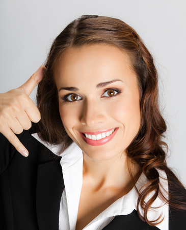 Young happy smiling businesswoman with call me gesture, over grey background. Business success concept.