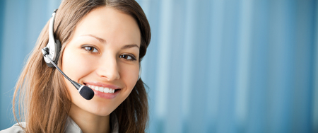 Portrait of happy smiling support phone operator in headset at workplace. Copyspace for slogan, big text or banner. Customer support service and consultation concept.
