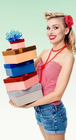 Portrait of beautiful young happy smiling woman in pin-up style clothing, holding gift boxes, on green background. Caucasian blond model posing in retro fashion and vintage concept shoot.