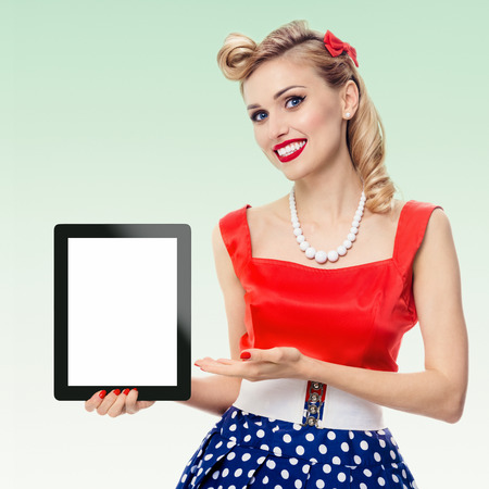 Woman, showing blank no-name tablet pc monitor, with copyspace, dressed in pin-up style dress in polka dot, on green background. Caucasian blond model posing in retro fashion vintage shoot.