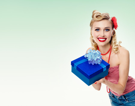 upsweep: Portrait of beautiful young happy smiling woman in pin-up style clothing, on green background. Caucasian blond model posing in retro fashion and vintage concept studio shoot. Copyspace area for advertising slogan or text message. Stock Photo