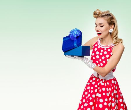upsweep: Young happy woman dressed in pin-up style red dress in polka dot and white gloves, on green background. Caucasian blond model posing in retro fashion studio shoot. Copyspace area for advertising slogan or text message.