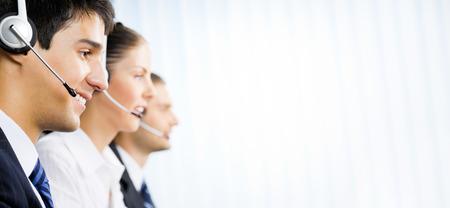Tre operatori telefonici felici del servizio clienti all'ufficio, con l'area del copyspace per testo, pubblicità o lo slogan. Servizio di consulenza e assistenza call center.