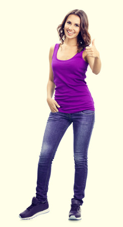 young woman smiling: Full body portrait of smiling beautiful young woman in casual smart lilac clothing, showing thumbs up gesture. Emotions concept.