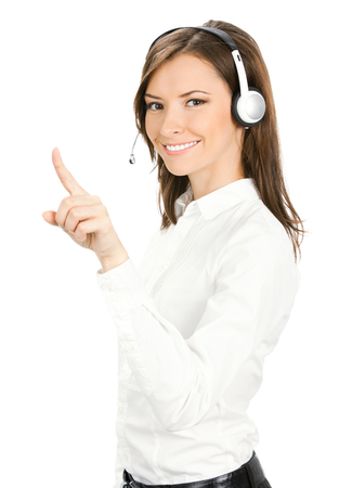 Call center. Portrait of happy smiling customer support service phone operator in headset pointing at something, isolated against white background. Stock Photo