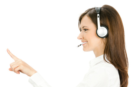 handsfree telephone: Call center. Portrait of happy smiling customer support service phone operator in headset pointing at something, isolated against white background. Stock Photo