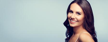 陽気な笑みを浮かべて若く美しい女性、灰色の背景上の肖像画。広告のスローガンやテキスト メッセージのための Copyspace エリア。