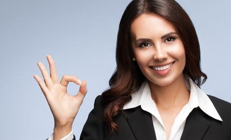 businesswoman suit: Portrait of happy smiling young businesswoman in black suit, showing okay gesture, over grey background. Brunette model in business success concept shot.