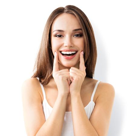 sonrisa: mujer joven que muestra la sonrisa, en la ropa elegante casual, aislado contra el fondo blanco Foto de archivo