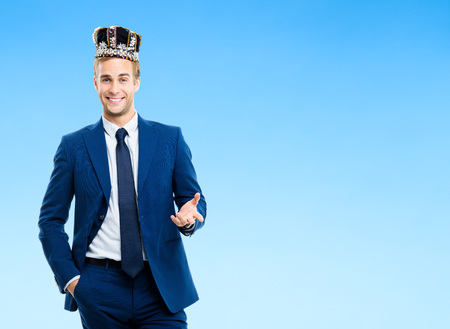 looking for job: I am business king! Portrait of happy smiling young businessman in crown, against blue background. Leadership and business success concept. Copyspace area for text or advertise slogan.