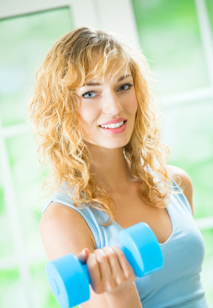 Portrait of young happy smiling beautiful woman in sportswear, doing fitness exercise with dumbbell, at home photo