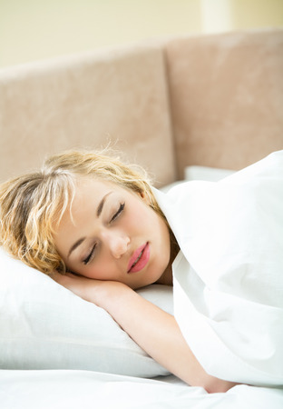 lazyness: Portrait of beautiful young sleeping woman at bedroom Stock Photo