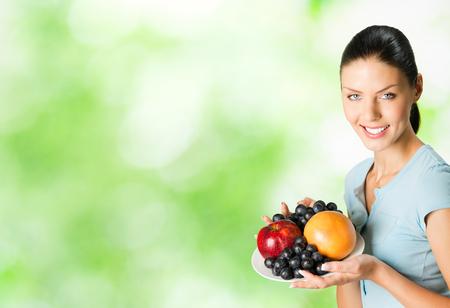 part of me: mujer sonriente feliz con placa de frutas, al aire libre. Para proporcionar la máxima calidad, he hecho esta imagen, por la combinación de dos fotos. Puede utilizar parte derecha de lema, texto grande o banner.